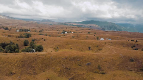 Aerial of hilly plateau in upland covered with dry grass. Clouds cover mountains Footage
