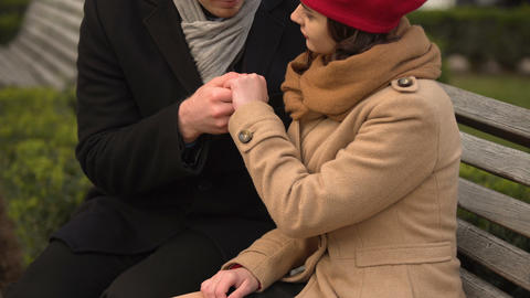 Handsome man kissing hand of his date, lovely couple on a bench, autumn park Footage