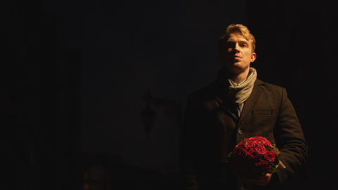 Angry disappointed man throwing away flowers for his date, relationship crisis Footage