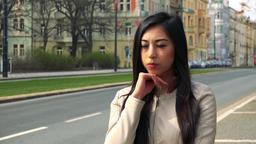 A young Asian woman broods over something in a street in an urban area Footage