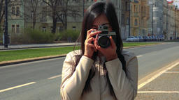 A young Asian woman takes a picture of the camera with her own camera and smiles Footage