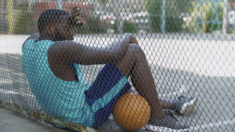 Tired African-American basketball player relaxing after game at stadium, hobby Live Action