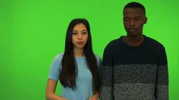 A young black man wraps his arm around a young Asian woman's shoulders, they Footage