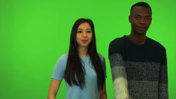 A young black man and a young Asian woman smile and show thumbs up to the camera Footage
