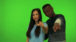 A young Asian woman and a young black man point at the camera and nod - green Footage