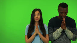 A young Asian woman and a young black man pray with hands clasped together - Footage
