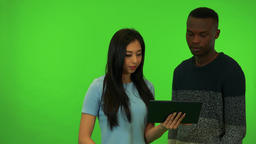 A young Asian woman and a young black man work on a tablet together - green Footage