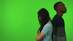 A young Asian woman and a young black man stand with their back against each Live Action