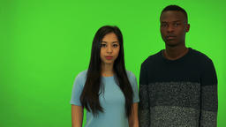 A young Asian woman and a young black man shake their heads at the camera - Footage
