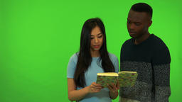 A young Asian woman explains to a young black man something about the book she Footage