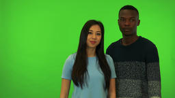 A young Asian woman and a young black man wave at the camera in a gesture of Footage