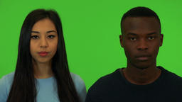 A young Asian woman and a young black man look at the camera - closeup on the Footage