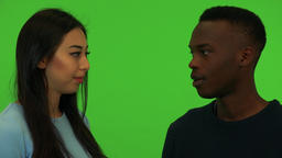A young Asian woman and a young black man talk - closeup on the faces - green Live Action