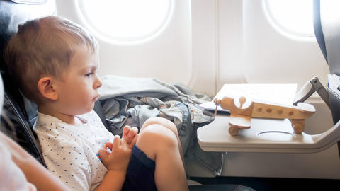 Portrait of 2 years old todler boy with toy wooden airplane during long flight Fotografía