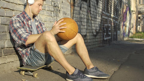 Active man sitting on skateboard, playing ball and listening to music in headset Live Action