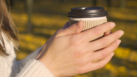 Girl warming hands and drinking coffee alone, enjoying sunny autumn, inspiration Live Action