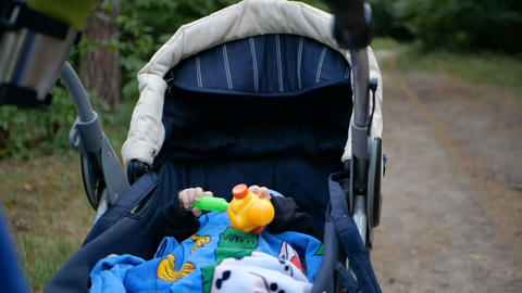 Child laying in the stroller and playing with toy in slow motion Footage