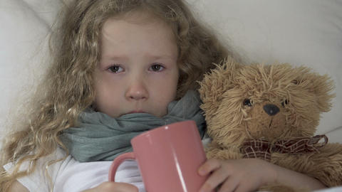 Crying ill girl lying in bed with toy bear, holding cup and looking into camera Footage