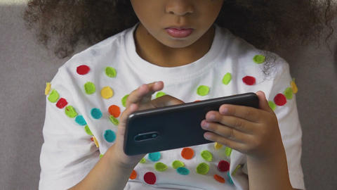Concentrated child tapping cell phone screen, interest in modern technology Footage