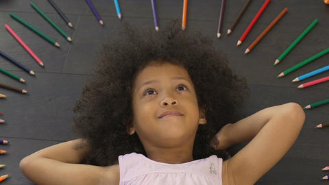 Small kid with big afro lying on floor and thinking of new idea, imagination Footage