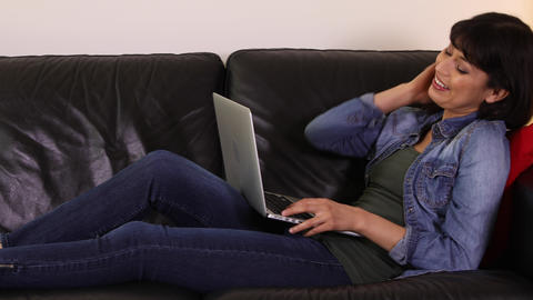 Woman Using Laptop Computer While Sitting On Couch Footage