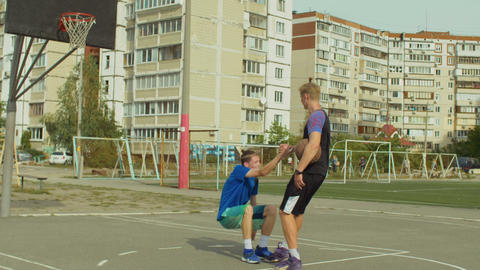 Streetball player helping fallen opponent to stand up Live Action