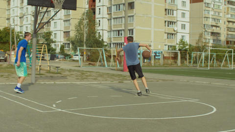 Teenagers training basketball skills on outdoor court GIF