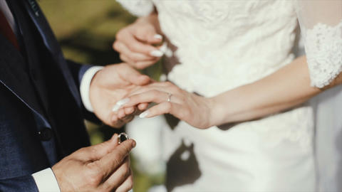 The groom puts the wedding ring on finger of the bride. marriage. hands with Live Action