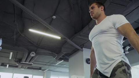 Handsome guy doing exercises with dumbbells in the gym Footage