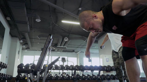 Two strong guys doing exercises in the gym Footage