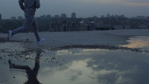 Athlete running through puddles without problems, reliable sports and footwear Live Action