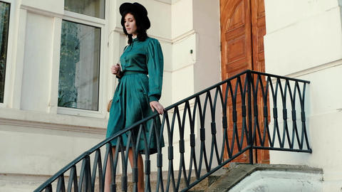 A girl in a vintage dress and hat near a historic building Live Action