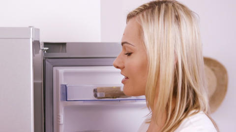 Blonde woman taking a yoghurt on the fridge Live Action