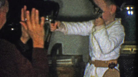1954: Kid holds up grandpa pulling dual revolver toy guns from holster Footage