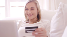 Blonde woman smiling and buying on internet Live Action