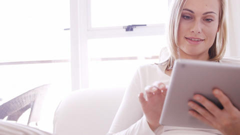 Blonde woman sitting on a sofa using a tablet Live Action