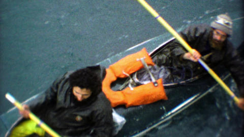 1974: Rugged mountain men paddle heavy ocean kayak to dock Footage
