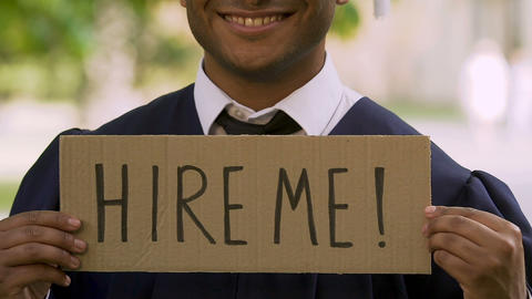 Graduate of prestigious university holding sign with inscription hire me, career Footage