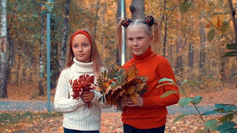 Portrait serious teenager girls with colored leaves in hands looking into camera Footage