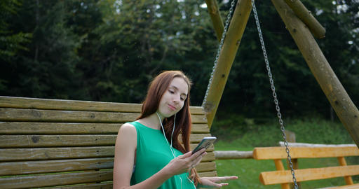Young girl listeting music on the swing GIF