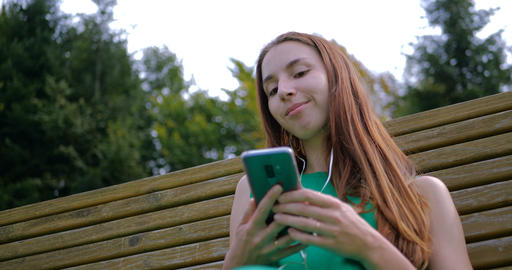 Young woman resting on the bench and listening music with headphones GIF