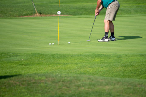 Golfer on the green, mature male, not recognizable, copyspace Photo