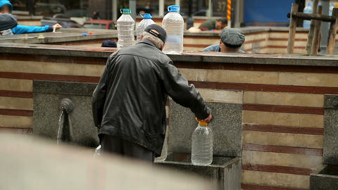 Local elderly men filling water tanks with mineral water, underground springs Footage