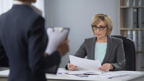 Strict serious lady boss looking contemptuously at secretary, poor performance Footage