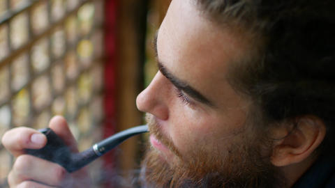 Close up of attractive man with beard smoking on the beach. Outside. Portrait Footage