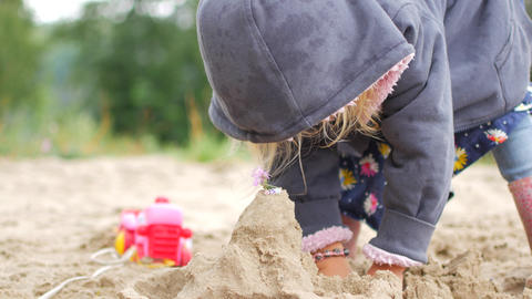 Children playing sand on the beach. Little girl builds sand castle by himself on Footage