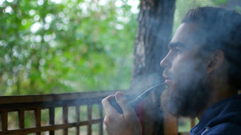 Close up of attractive man with beard smoking on the... Stock Video Footage