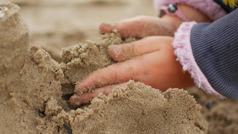 Children playing sand on the beach. Little girl builds sand castle by himself on Live Action