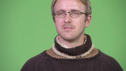 Blonde handsome man thinking while wearing turtleneck sweater and eyeglasses Footage
