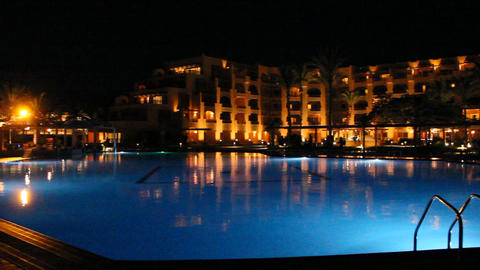 Lights of evening hotel are reflected in pool water in night. Bright lights of Footage